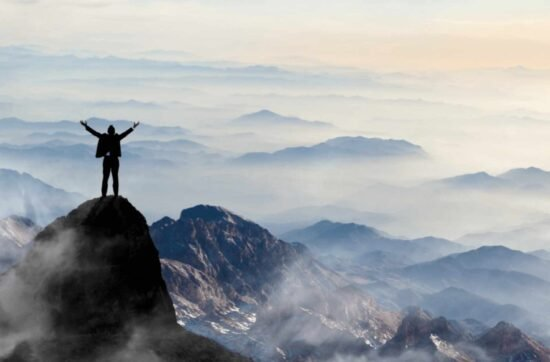 Mann auf Berg mit Weitsicht, Arme in die Luft gestreckt